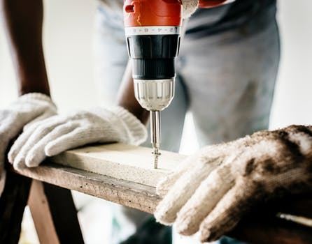 Drill moving into wood in a joinery workshop.