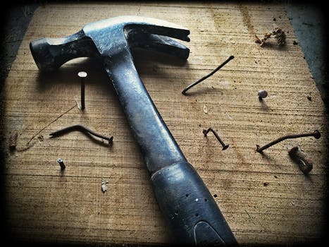 A traditional joinery hammer lies on a wooden palette with nails