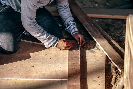 Man kneeling on top of sheets of wood in his joinery workshop.