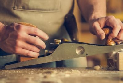 Close up of a joinery workshop with a man slicing into wood.