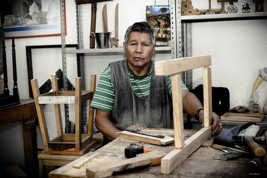 Man sits in joinery workshop with a wooden frame mid-project laid out in front of him.
