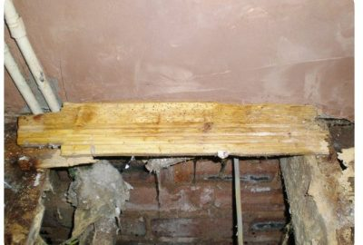 Close look at timber affected by woodworm and the area that will receive woodworm treatment.